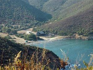 Plaža je ušuškana između zelenih brda